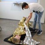 Erste Hilfe Kurs Shülerin wird in Rettungsdecke gewickelt